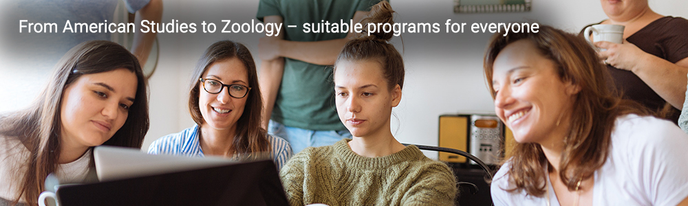 Slider: Photo which shows a group of people looking at a laptop. Inscription: From American Studies to Zoology – suitable programs for everyone